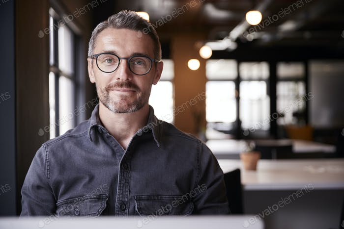 Middle aged white male creative sitting in an office smiling to camera, head and shoulders, close up