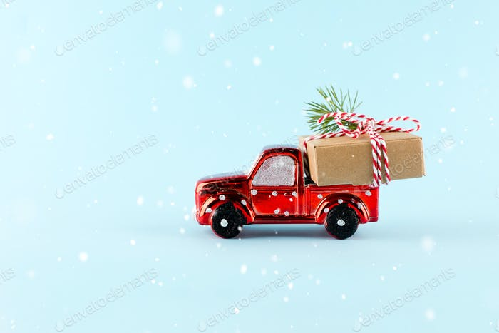 Red toy car delivering Christmas or New Year gift present box on blue background.