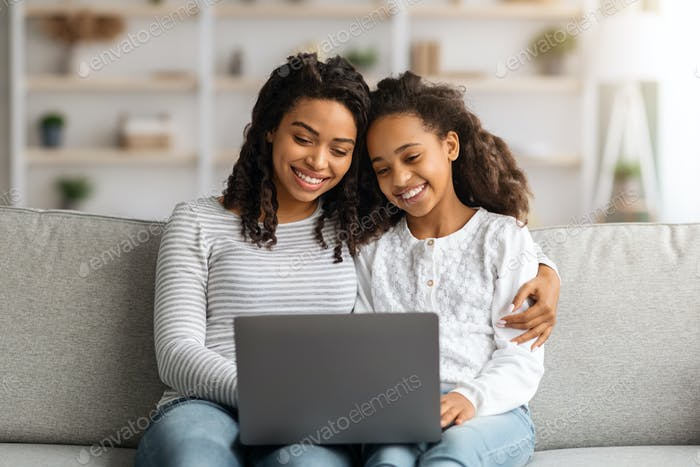 Happy african american mother and daughter using laptop together