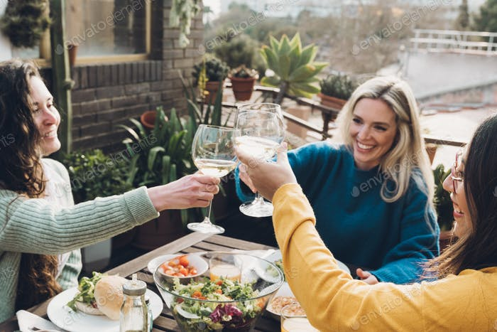 Young multiracial people cheering with wine and eating outdoors at patio restaurant