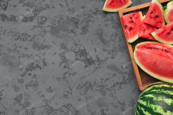 Ripe fresh watermelon slices in wooden box on grey concrete table