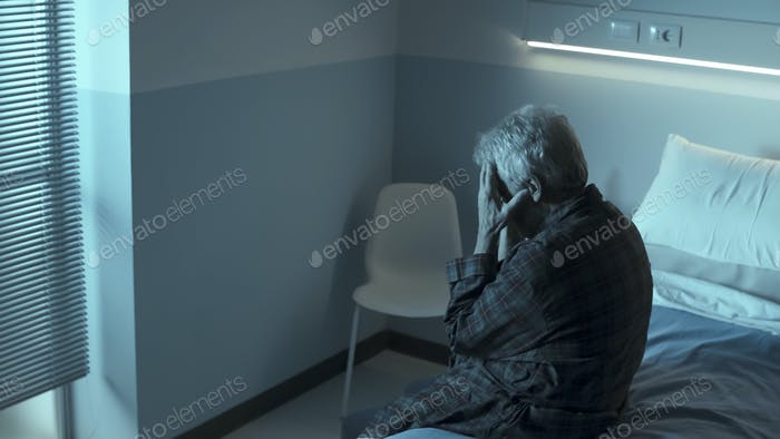 Sad lonely senior sitting in a hospital bed at night