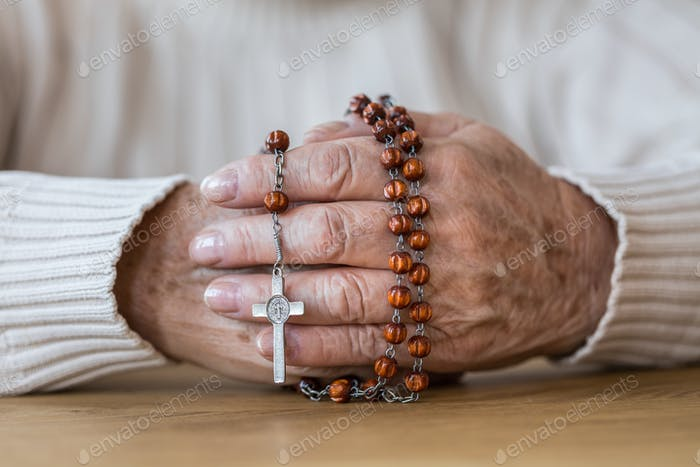 Senior's hands with red rosary