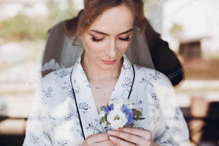 beautiful happy bride holding and looking at stylish boutonniere by the window