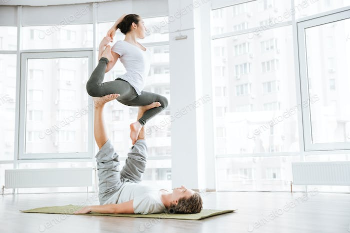 Concentrated young man and woman doing acro yoga for couples