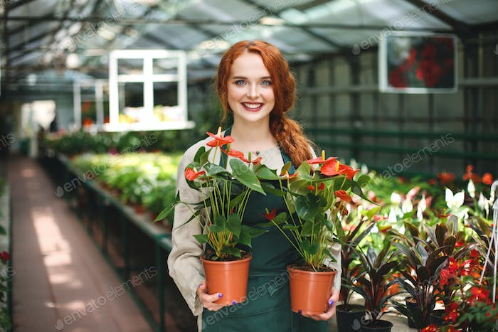 Beautiful smiling florist in apron standing with two flowers in pots