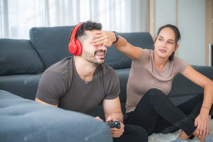 happy family concept, young couple having fun and enjoying to playing video game with gamer joystick