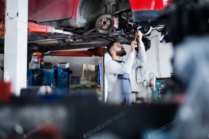 Mann Mechaniker reparieren ein Auto in einer Garage.
