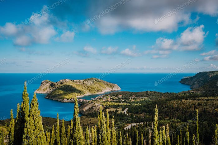 View to Assos village in sun light and beautiful blue sea. Green cypress trees in foreground