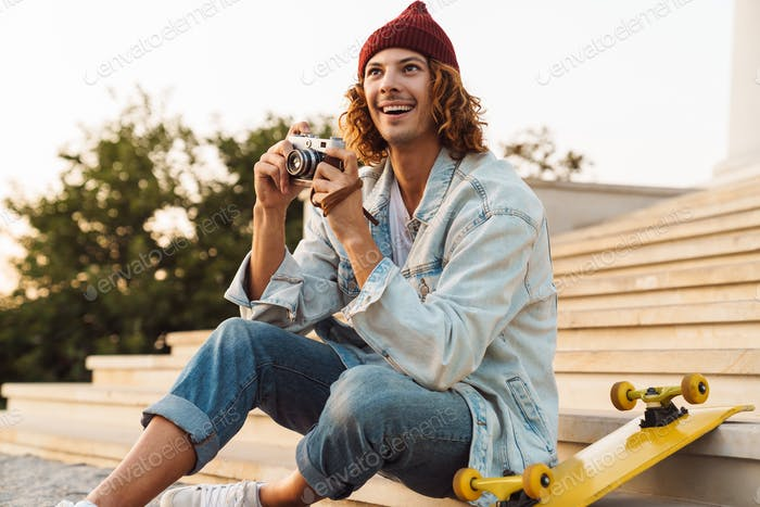 Happy young curly man scater holding camera