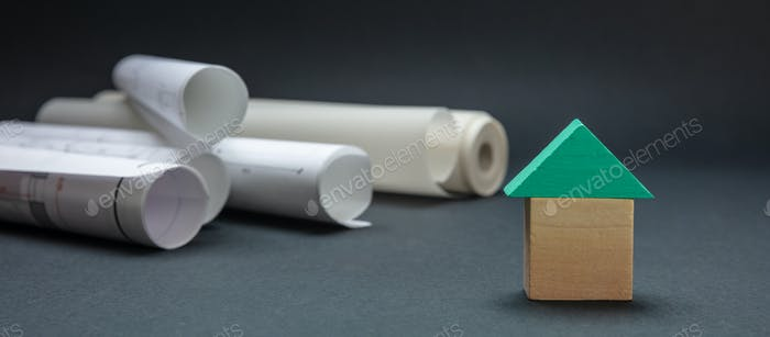 Small house with roof model and project blueprints on black color background