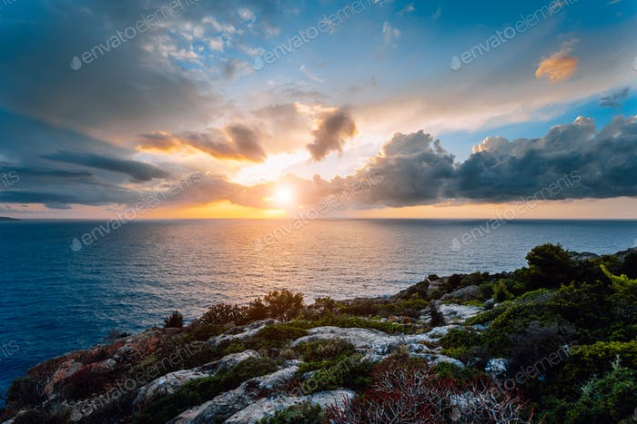 Dramatic moody sunset on the coastline near Assos place on Kefalonia Island. Motion clouds on