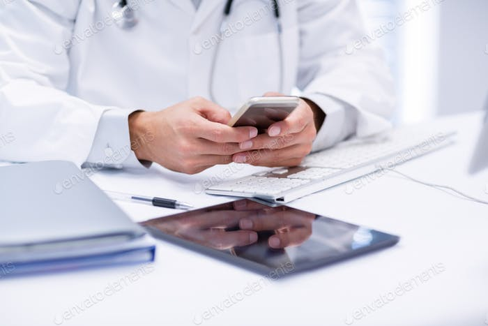 Mid section of doctor using mobile phone