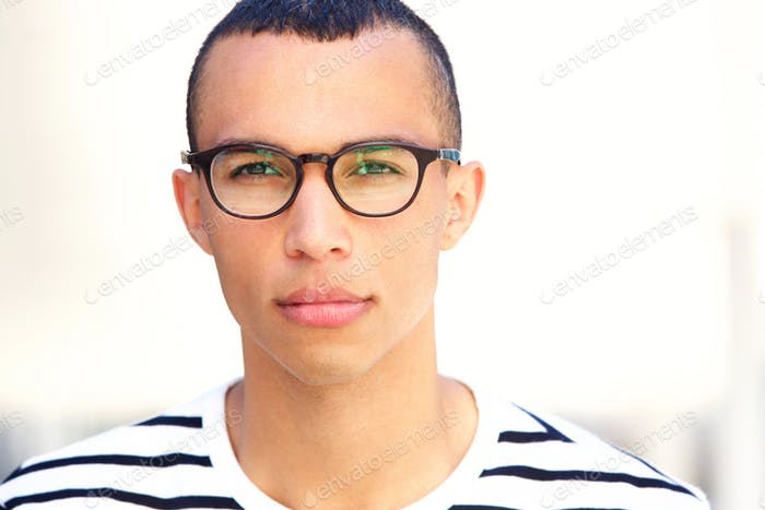 Close up front portrait of young man with glasses