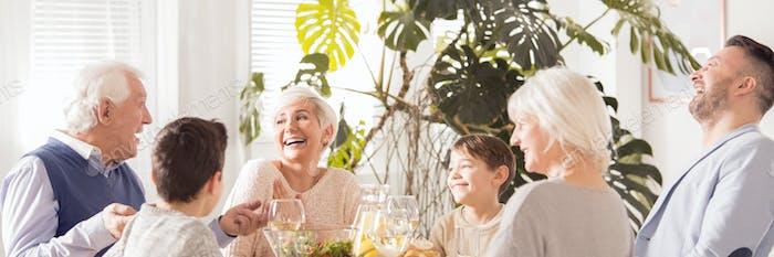 Laughing family eating dinner
