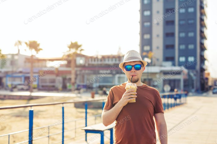 man in sunglasses drinking coffee frappe from disposable paper cup outdoors