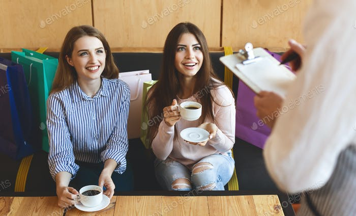 Two cheerful girls making order in cafe and drinking coffee