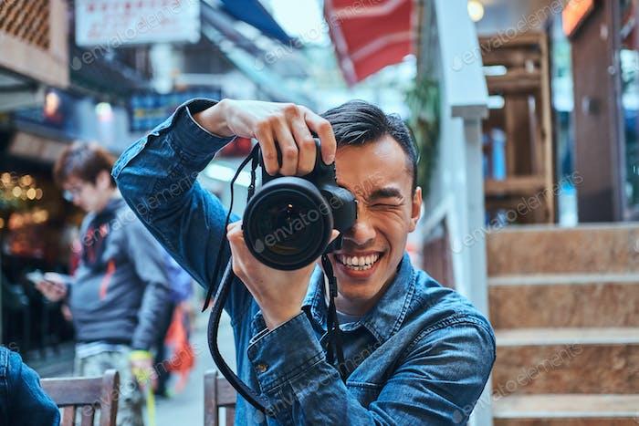 Porträt eines jungen Mannes mit Fotokamera