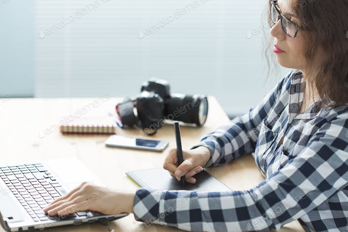 Business, technology and people concept - woman use designer tablet in working at laptop