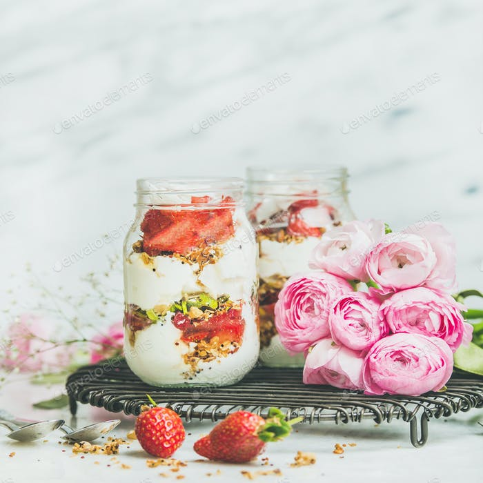 Healthy spring breakfast jars with pink raninkulus flowers, square crop