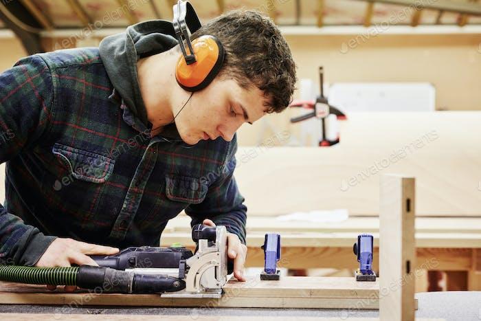 Un joven que usa herramientas para dar forma a un pedazo de madera en un taller de muebles.