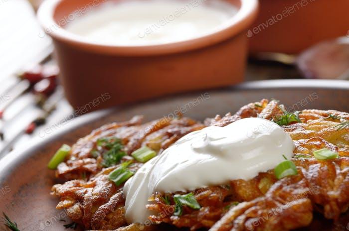 Closeup photo of fresh homemade potato pancakes in clay dish wit