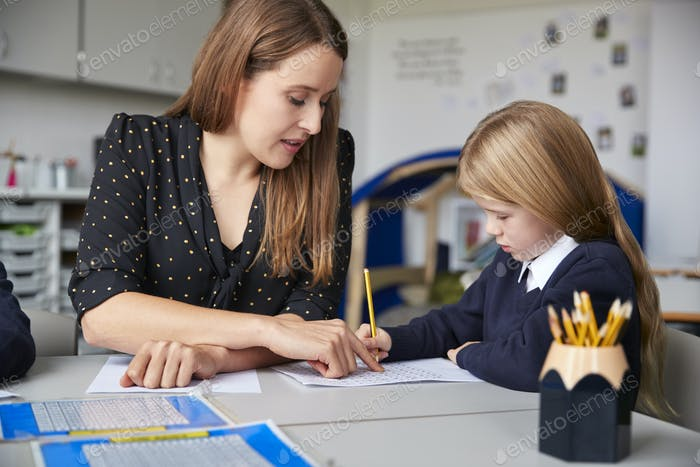 Female primary school teacher sitting at a table in a classroom with a schoolgirl