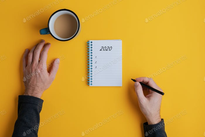 Top view of a man writing down plans or resolutions for the year 2020