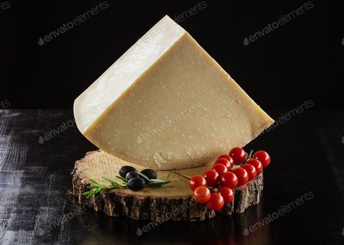 Piece of hard cheese, cherry tomatoes and olives on wooden board