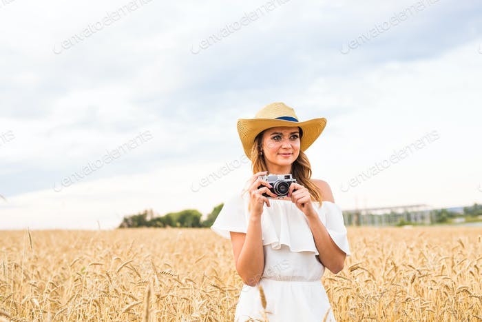 female photographer in the field with a camera taking pictures