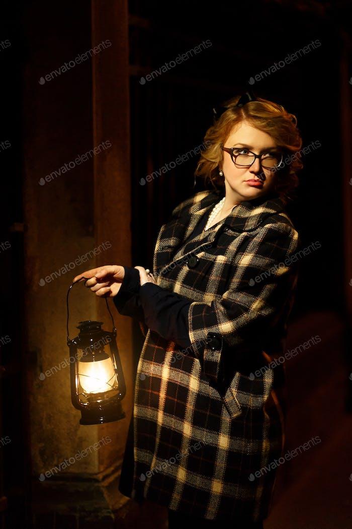 Mysterious blonde woman in elegant retro coat with old oil lantern walking in old street