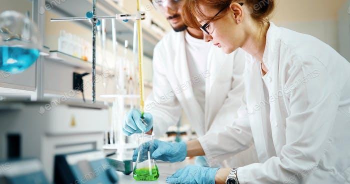 Junge Studenten der Chemie, die im Labor arbeiten