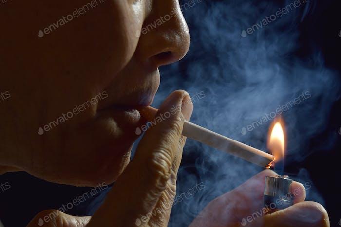 Человек, зажигающий сигарету с зажигалкой