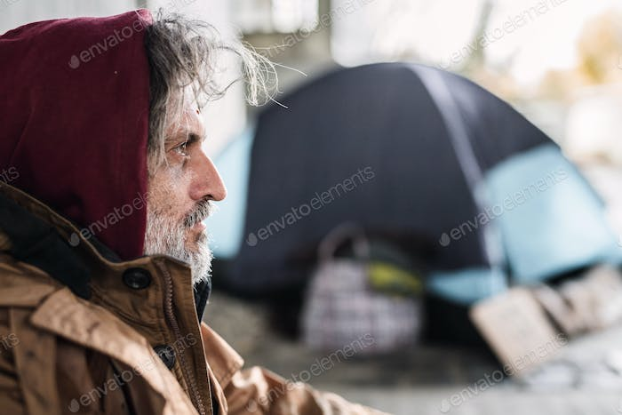 A side view portrait of homeless beggar man sitting outdoors. Copy space.