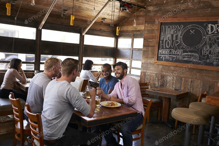 Four male friends sitting at lunch together in a restaurant