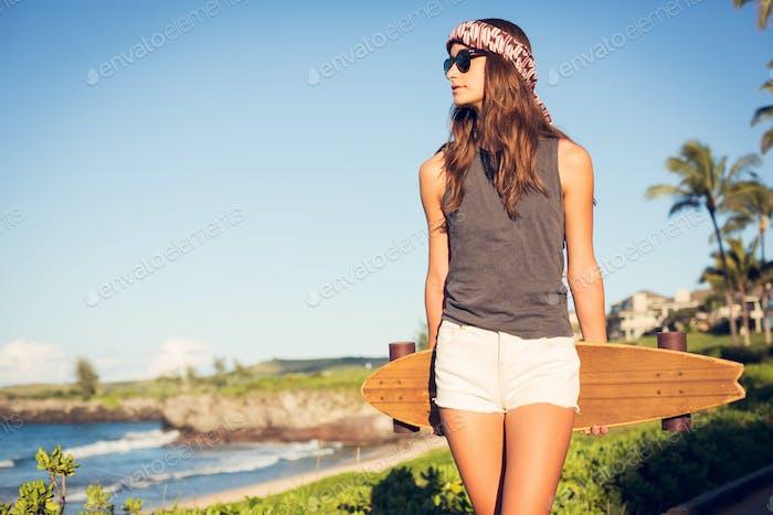 Schöne junge Frau mit einem Skateboard