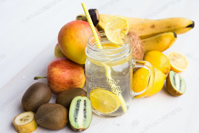 Glass of fresh lemonade in an environment of fruits