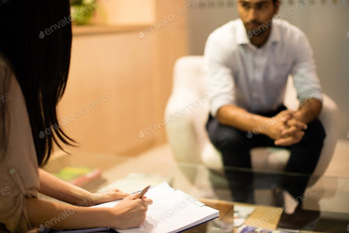 Businesswoman writing on clipboard while discussing with male colleague