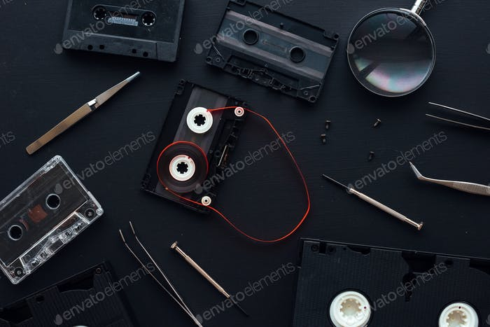 Flat lay audio and video cassette parts on dark background