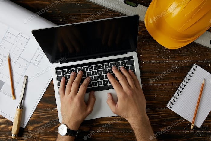 cropped image of architect typing on laptop at table with chisel, spirit level, protective helmet,