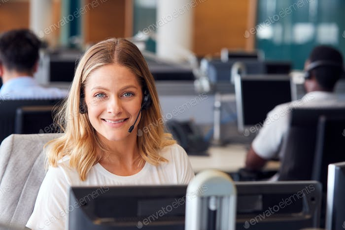 Portrait Of Businessman Wearing Telephone Headset Working In Customer Services Department