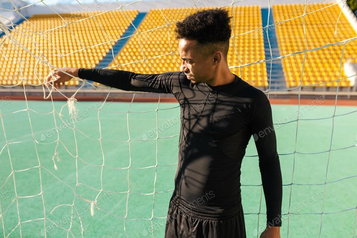 Young handsome African American sportsman standing in football goal at city stadium