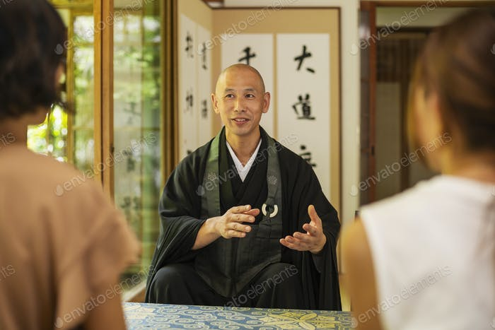 Two Japanese women and Buddhist priest kneeling in Buddhist temple, talking.