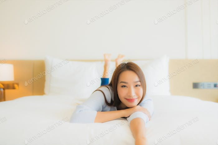 Portrait beautiful young asian woman smile relax leisure on bed