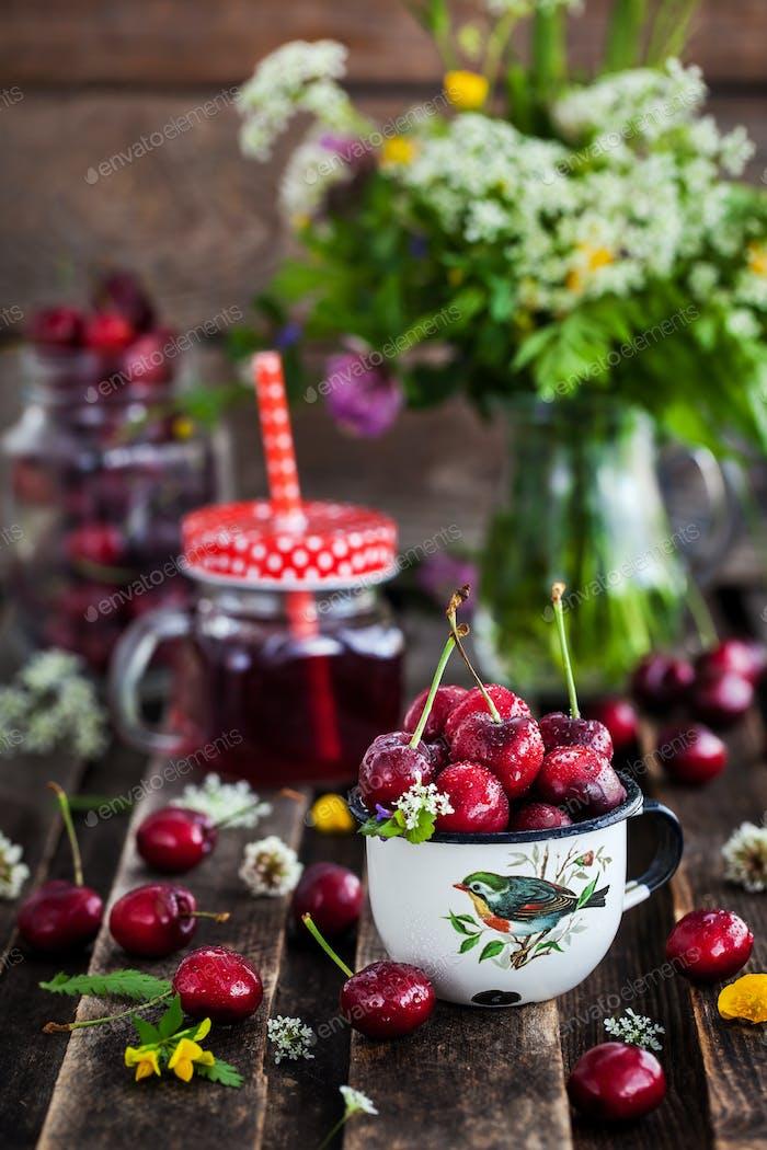 Fresh wet cherry in enamel metal mug