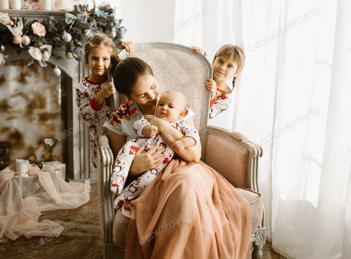 Beautiful mother sits with her little baby in the armchair next to the fireplace in the light cozy