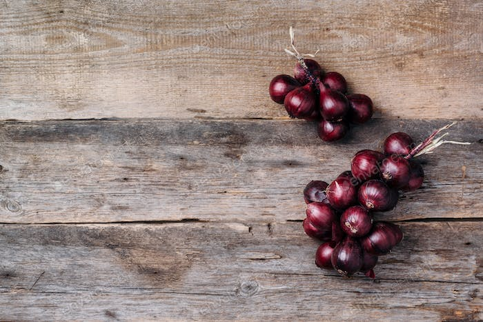 Bunch of purple onions on wooden background. Top view. Copy space. Autumn harvest