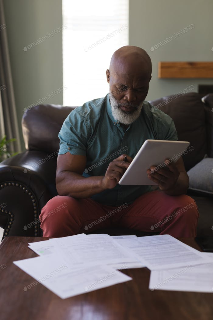 Front view of senior man filling form while using digital tablet in living room at home