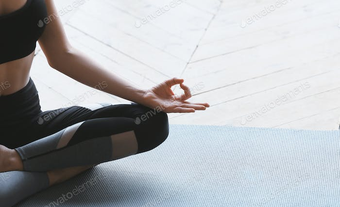 Yoga girl in lotus asana meditating at home