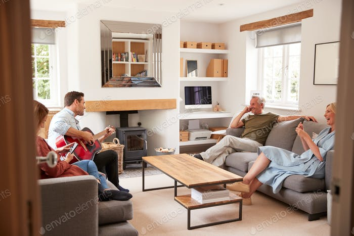 Family With Senior Parents And Adult Offspring Relaxing In Lounge At Home Together